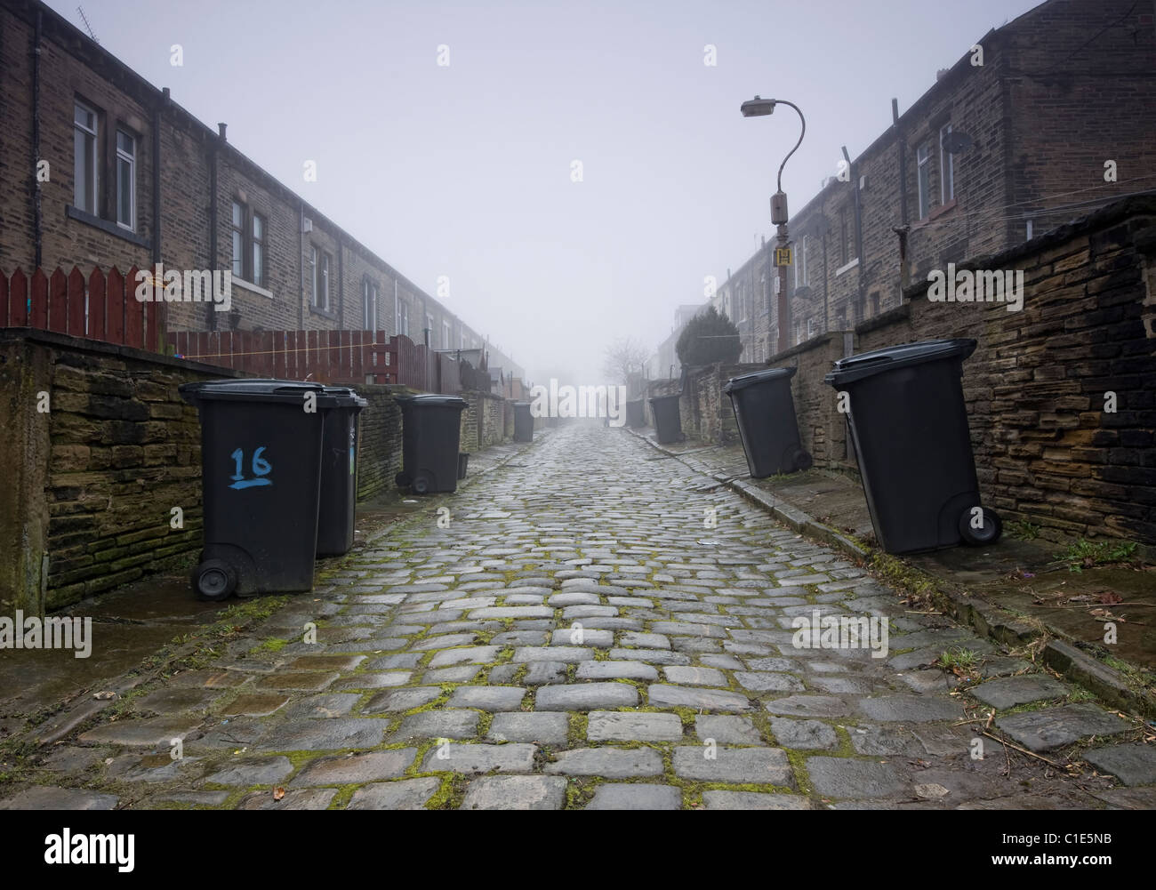back to back terraced housing on a cobbled street with vintage lamppost in northern town. - Stock Image