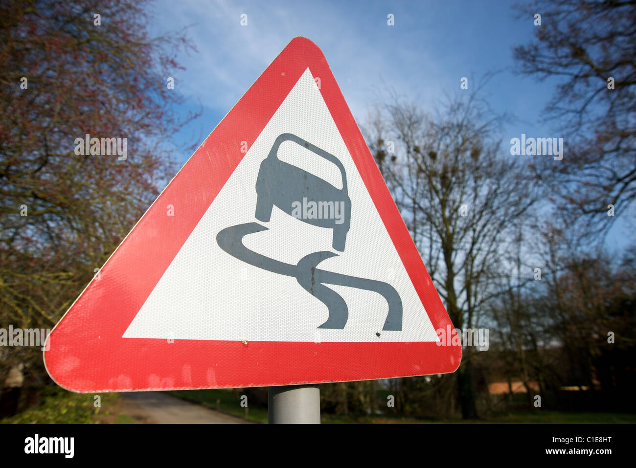 A road sign warning of a slippery road ahead, Warwickshire, England, UK - Stock Image