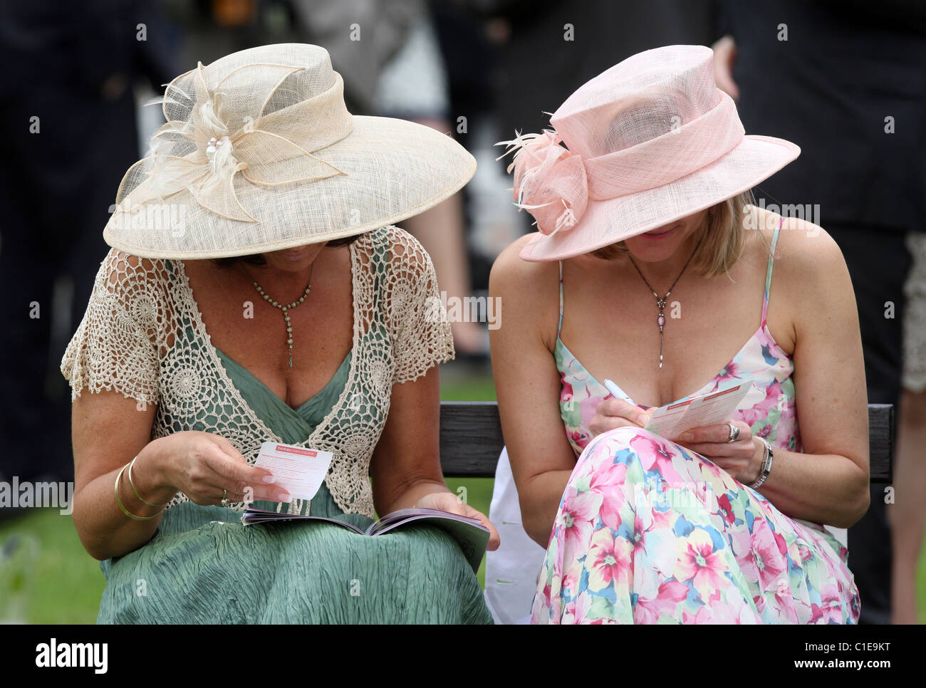 Women with hats and betting slips at a horse race, Epsom, United Kingdom - Stock Image