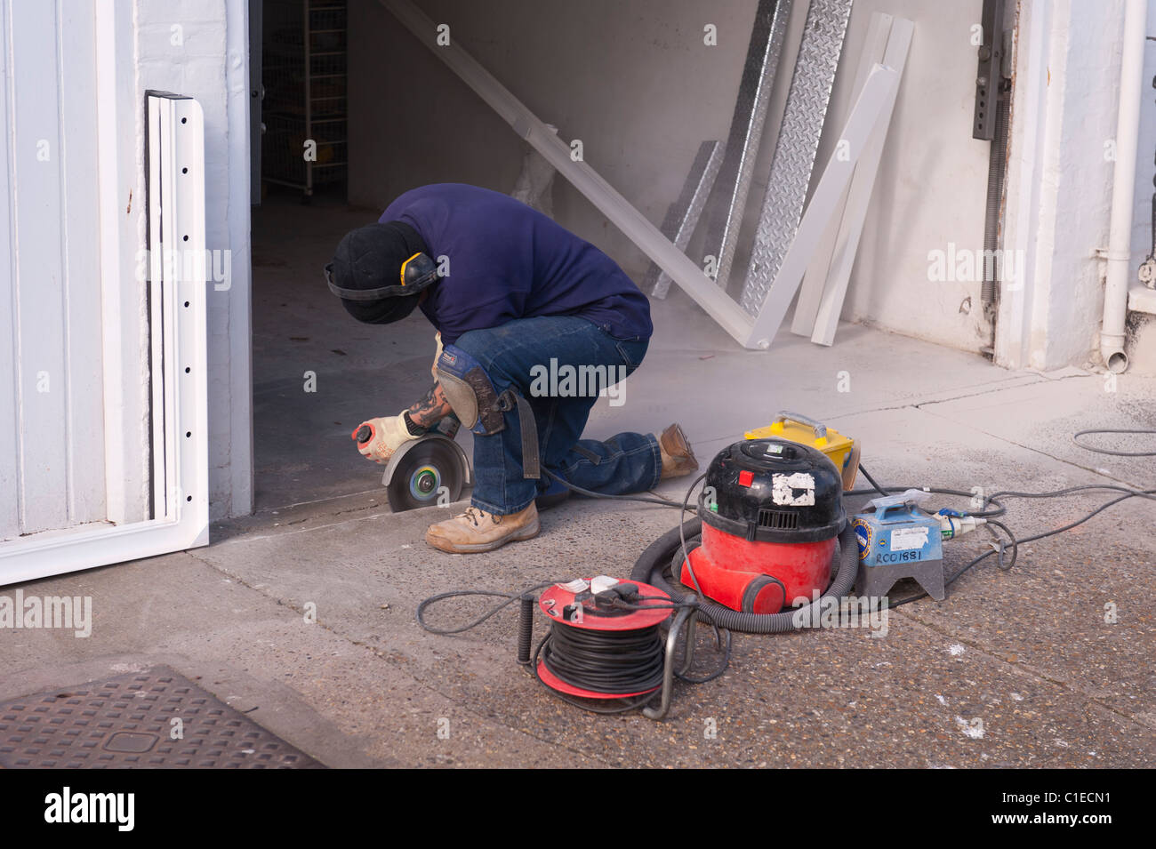 A builder using an angle grinder to cut through a concrete floor in the Uk - Stock Image