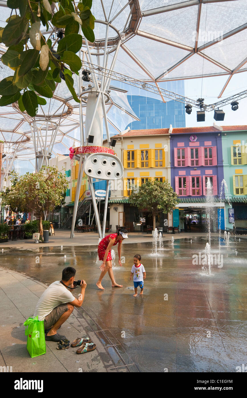 Family playing in the fountain at Clarke Quay, Singapore - Stock Image