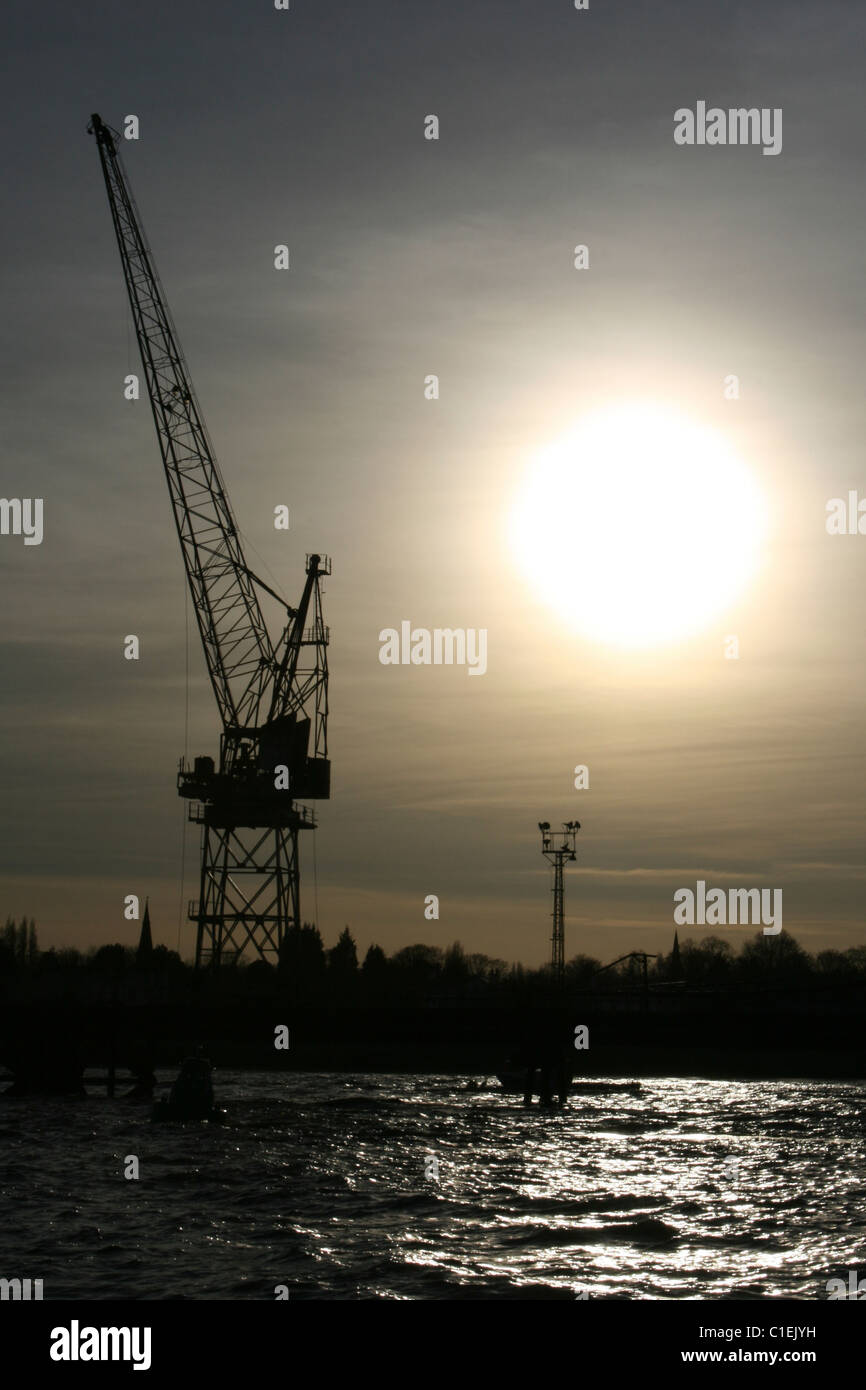 A Crane In Silhouette, River Mersey, Liverpool, UK - Stock Image