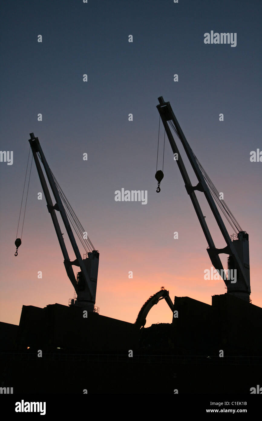 Ship Cranes Silhouetted At Sunset, Liverpool Docks, UK - Stock Image
