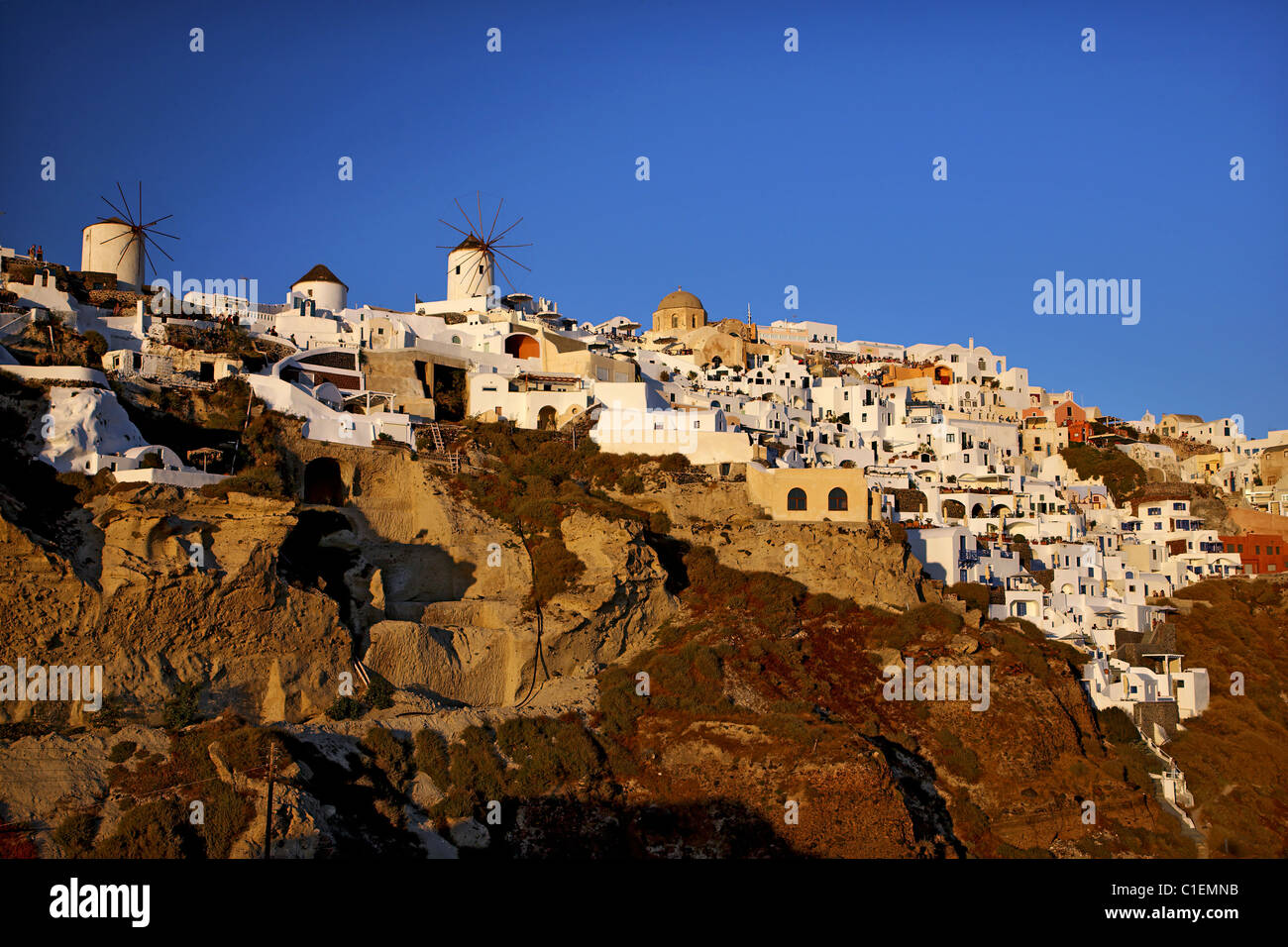 View of the eastern part of Oia village with its famous windmills around sunset. Santorini island, Cyclades, Greece - Stock Image