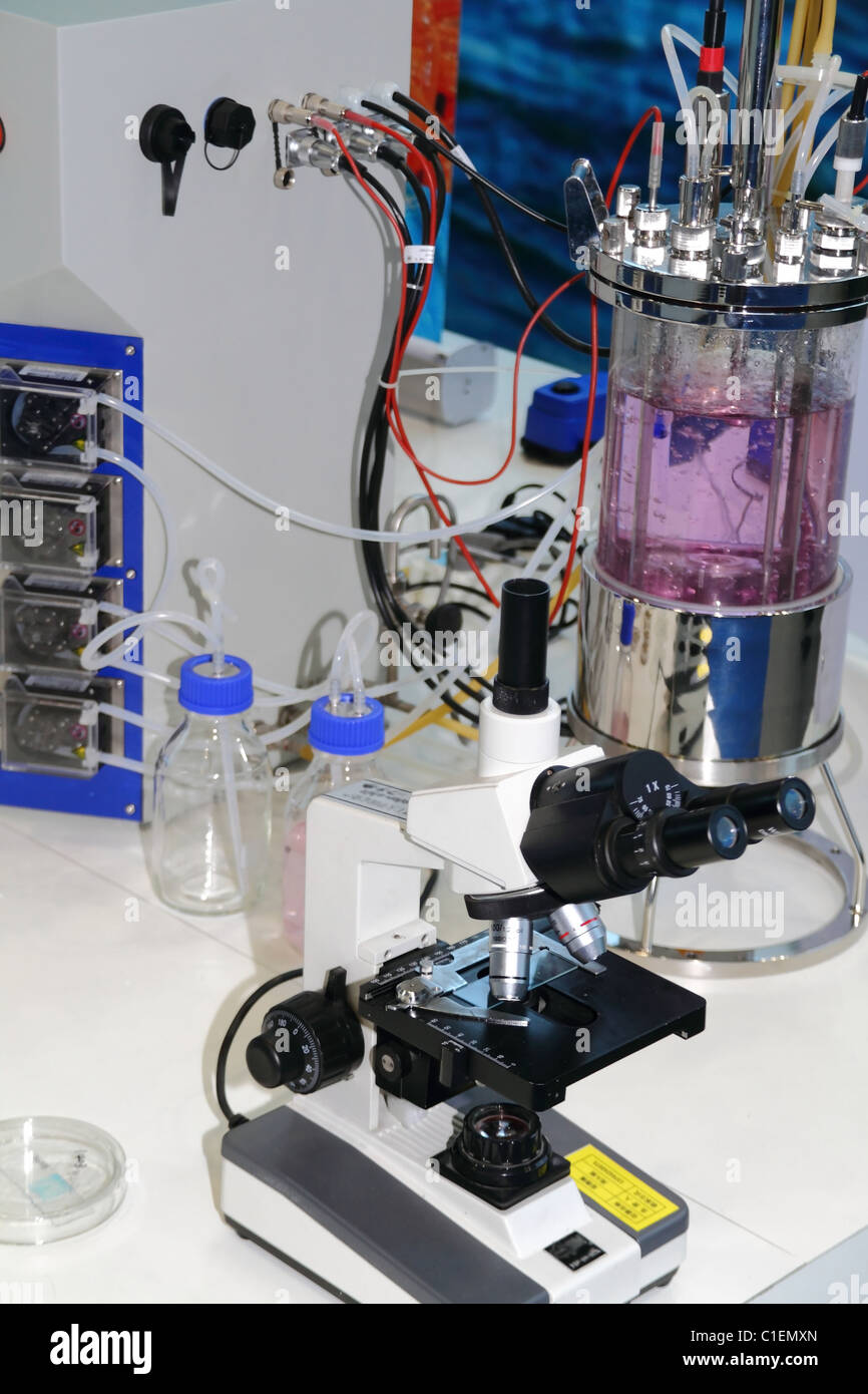 research microscope and laboratory bottles with colored liquid - Stock Image