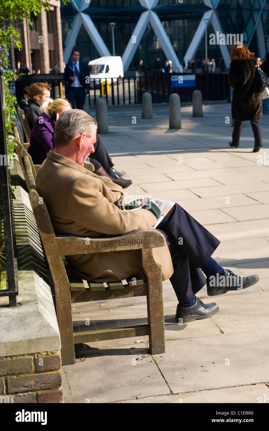 City of London , city gent or type in camel hair coat on wooden park bench doing Times crossword in lunchtime spring - Stock Image
