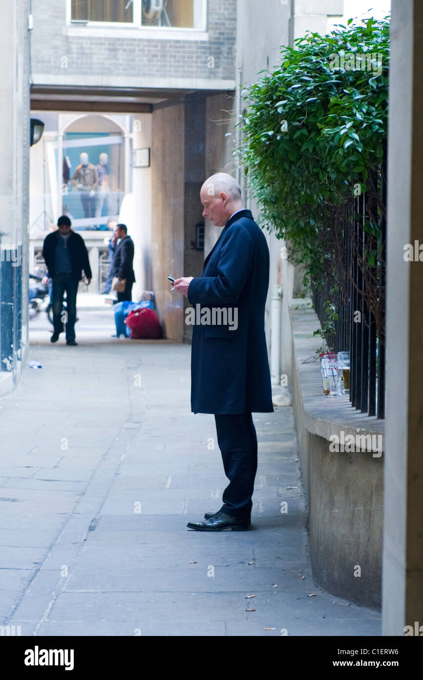 City of London , lunch break with beers City character or type or gent with mobile or cell phone - Stock Image