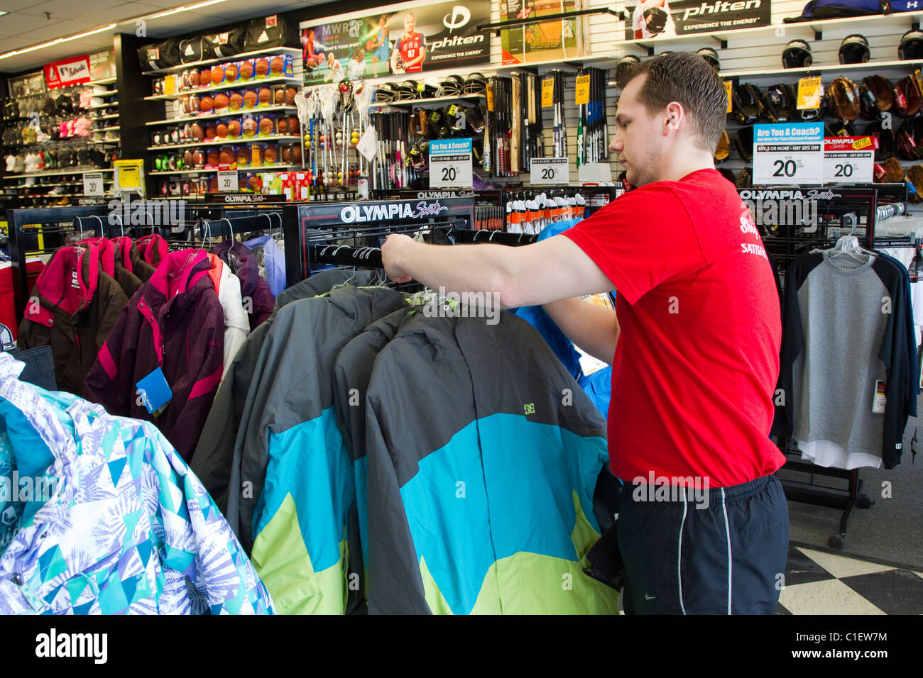 Athletic supply store manager arranges sports clothing placement in athletic sports store Stock Photo