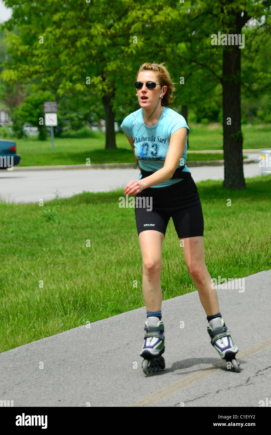 Woman inline skating in a forest preserve in Schaumburg, Chicago, Illinois, USA. Stock Photo