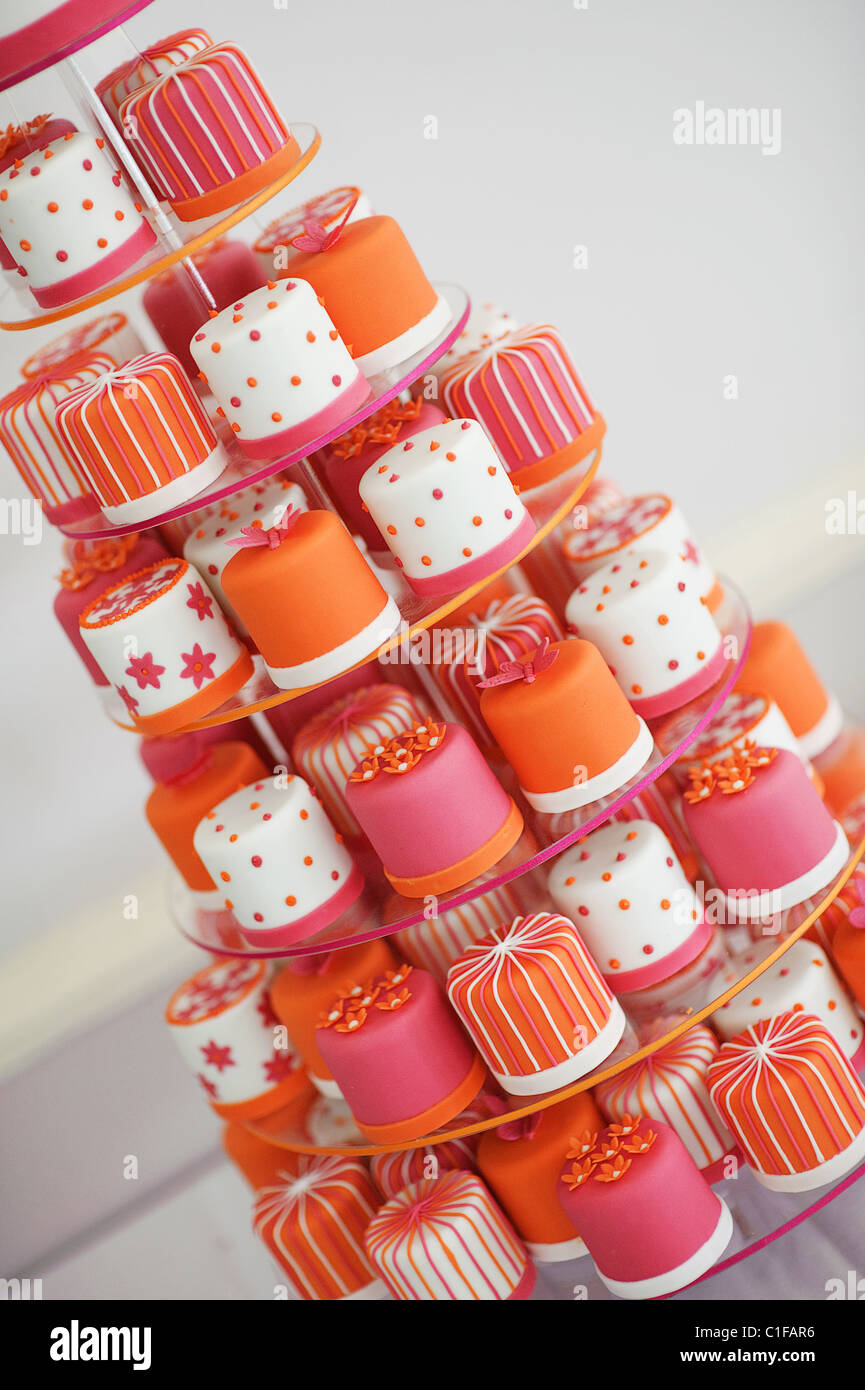 tier of mini decorated wedding cup cakes in orange and pink on a cake stand with stripes spots and stars - Stock Image