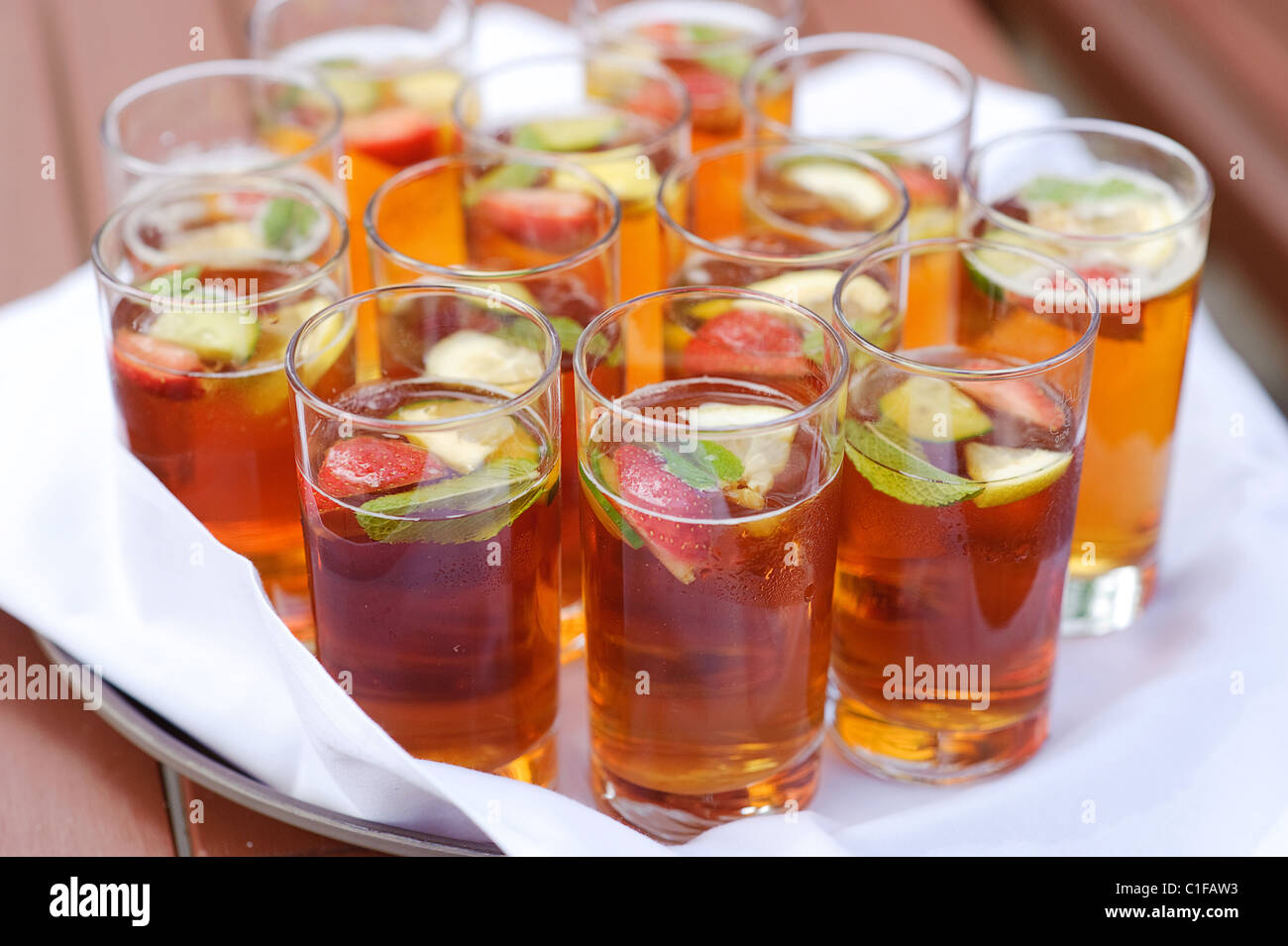 glasses on a tray with pimms cocktail fruit - Stock Image