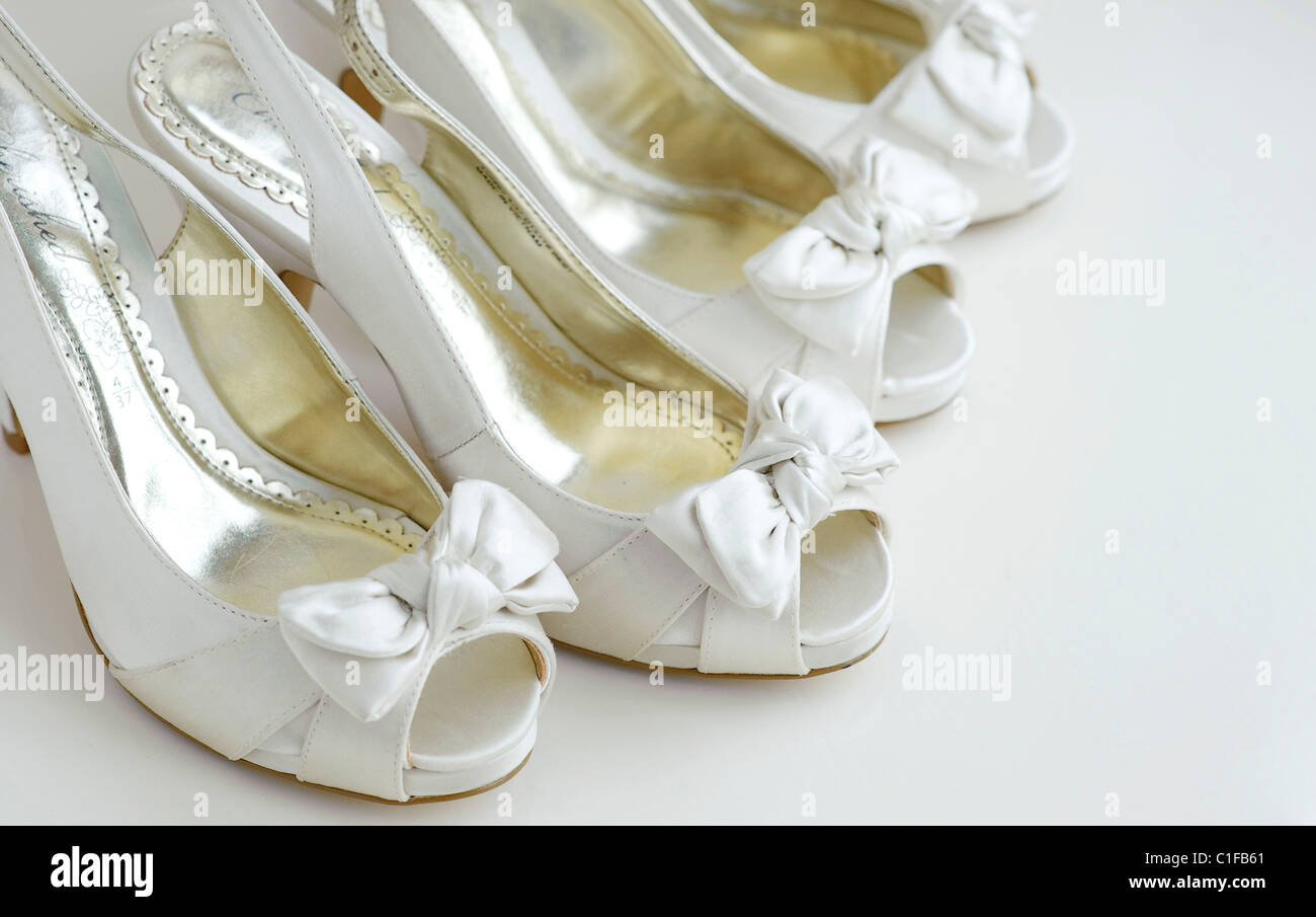 two pairs of ivory bridal shoes for bridesmaid on a white background with peep toe and bows on the front Stock Photo