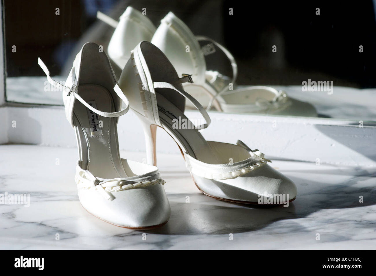 pair of white cream colored stiletto wedding bridal shoes on a marble shelf against a mirror Stock Photo