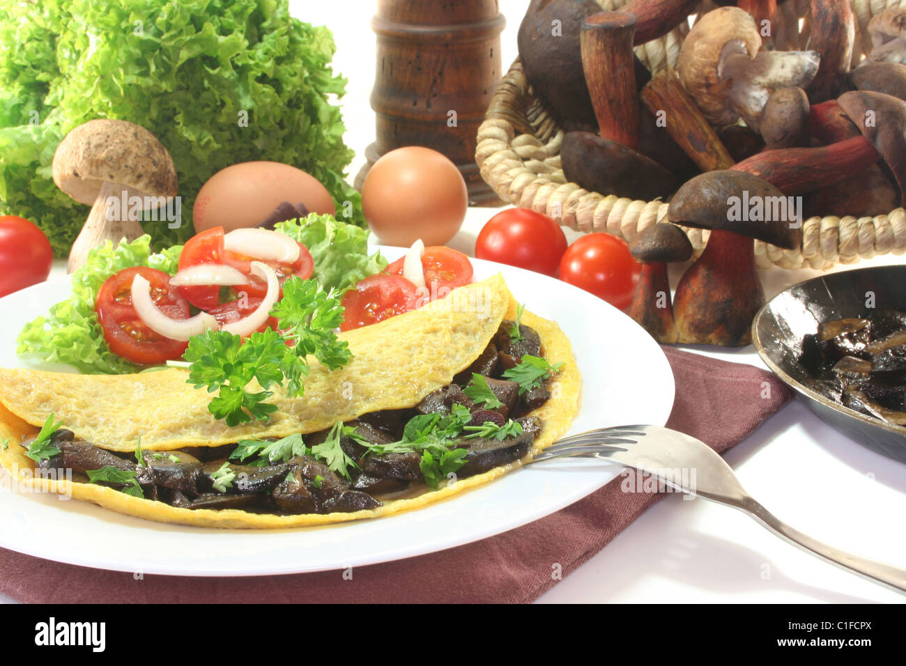 an omelet stuffed with wild mushrooms and fresh salad - Stock Image