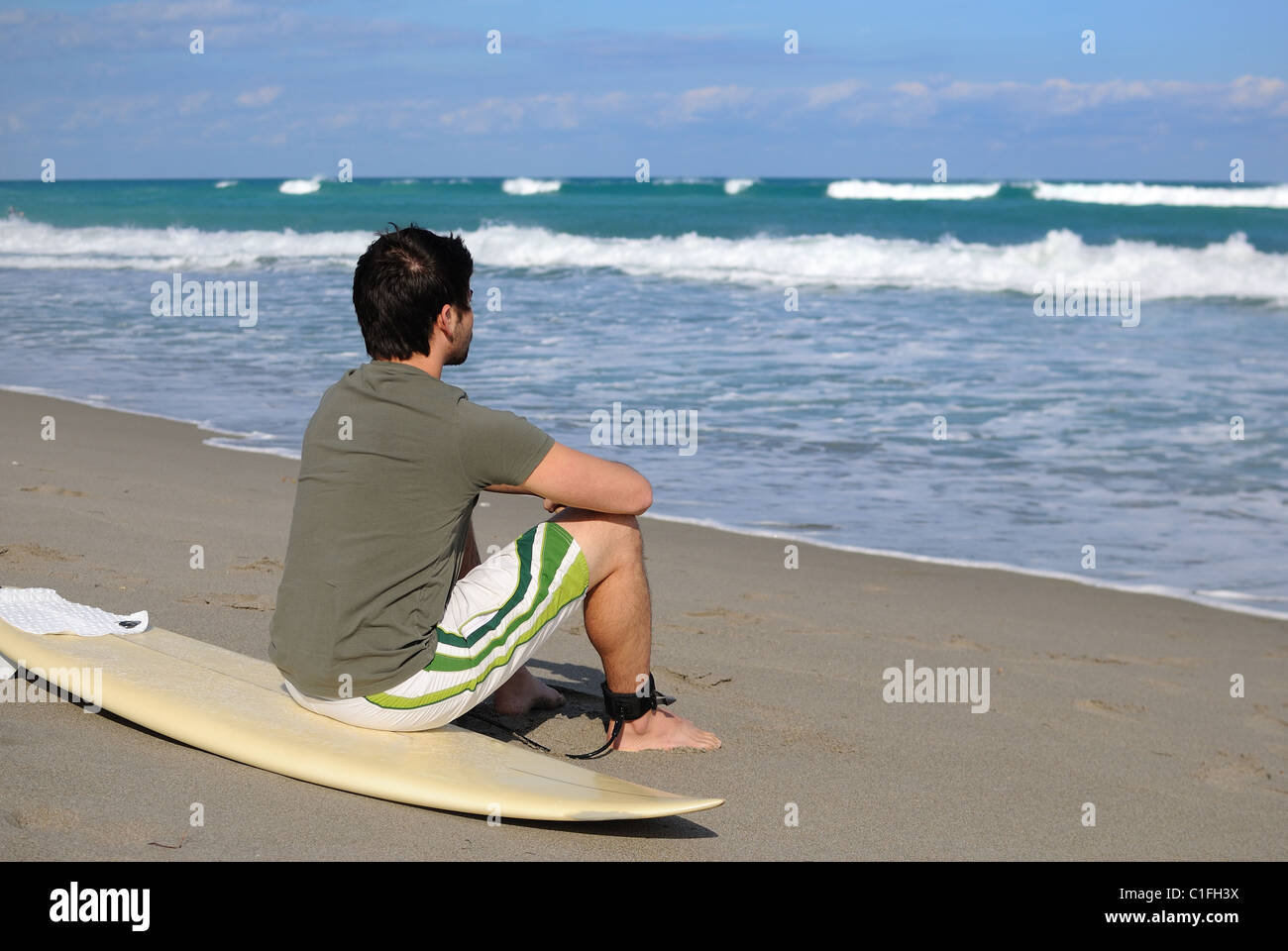 Surfer on the beach with his board. Stock Photo