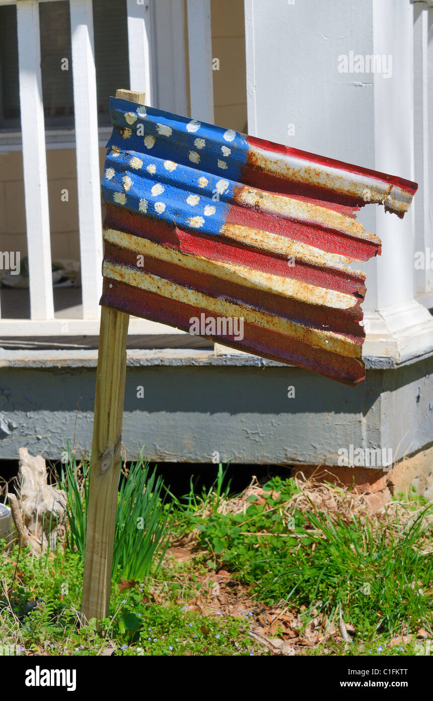 Rusted American flag on a residential lawn. - Stock Image