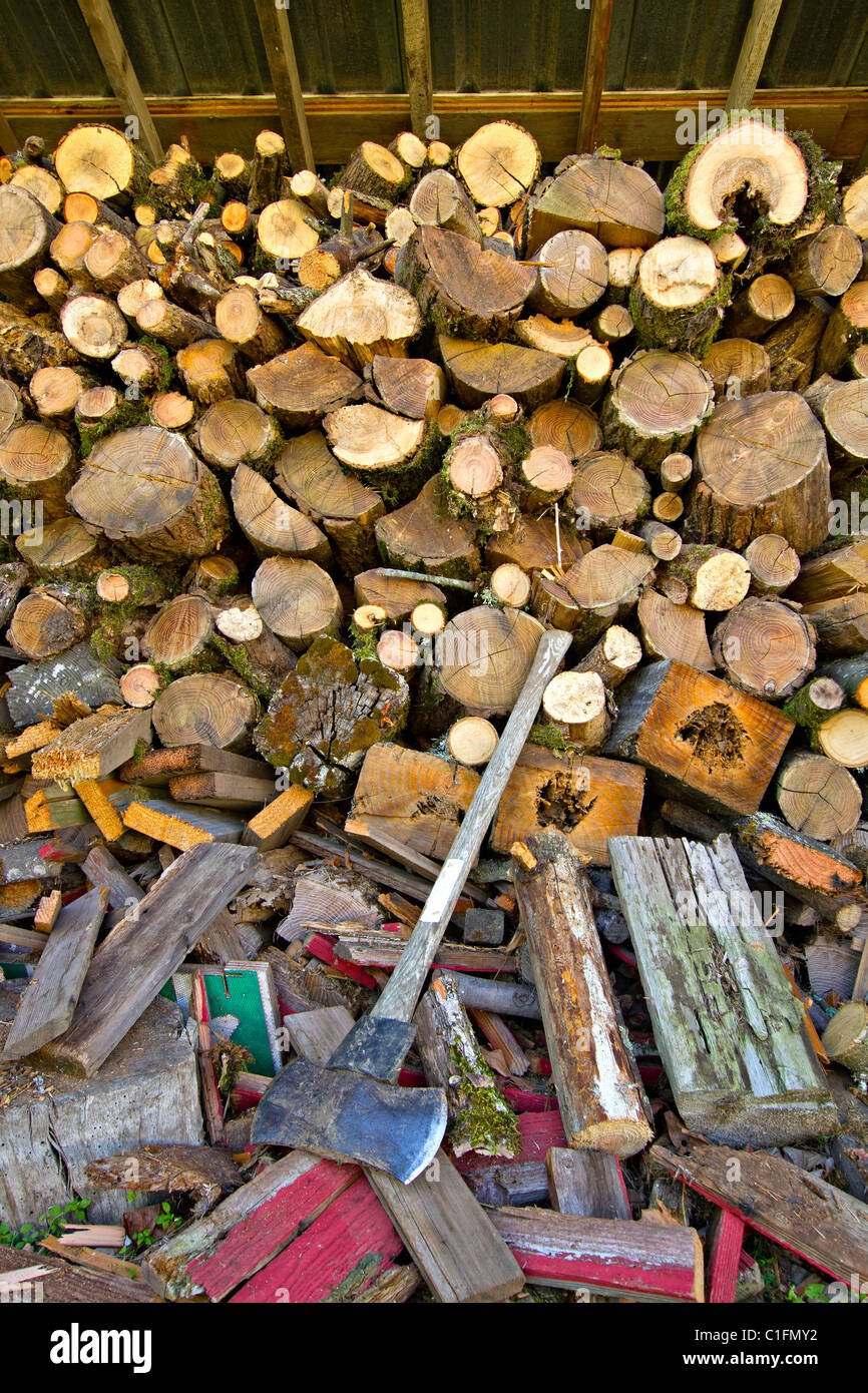 Piles of Firewood with Chopping Axe on Oregon Farmland - Stock Image
