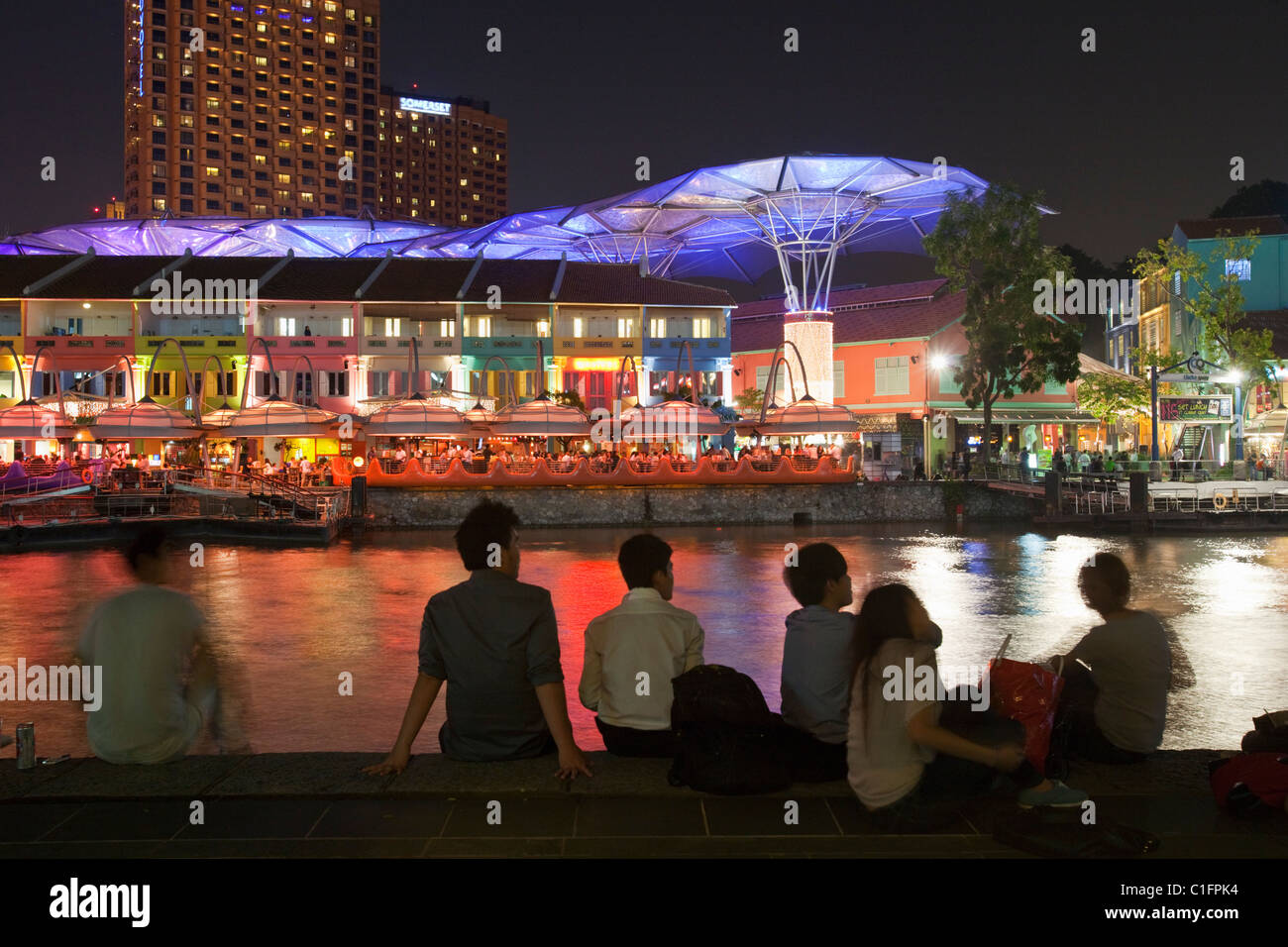People relaxing at the riverside district of Clarke Quay, Singapore - Stock Image