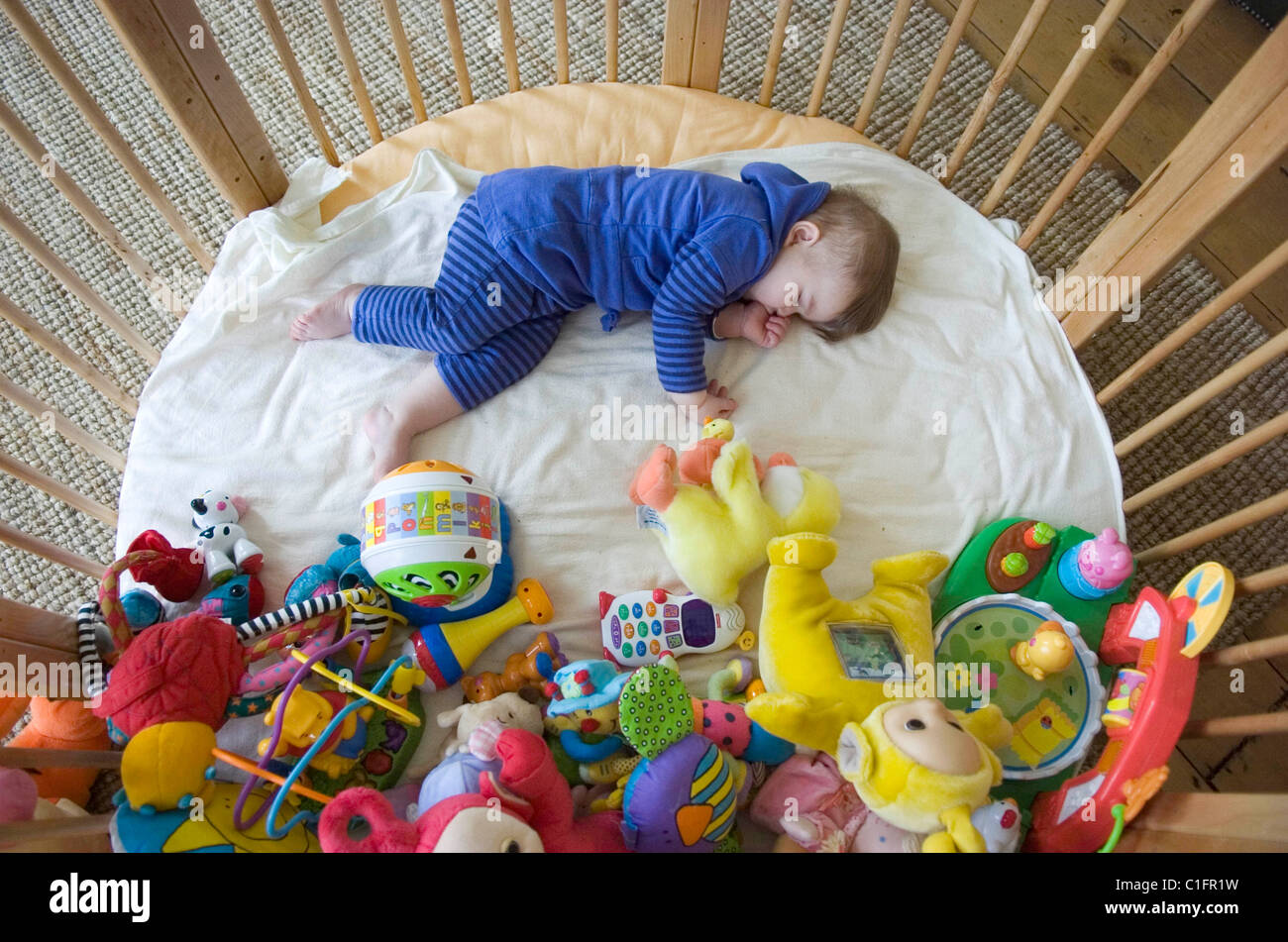 One Year Old Baby Girl Asleep In Her Playpen Surrounded By All The