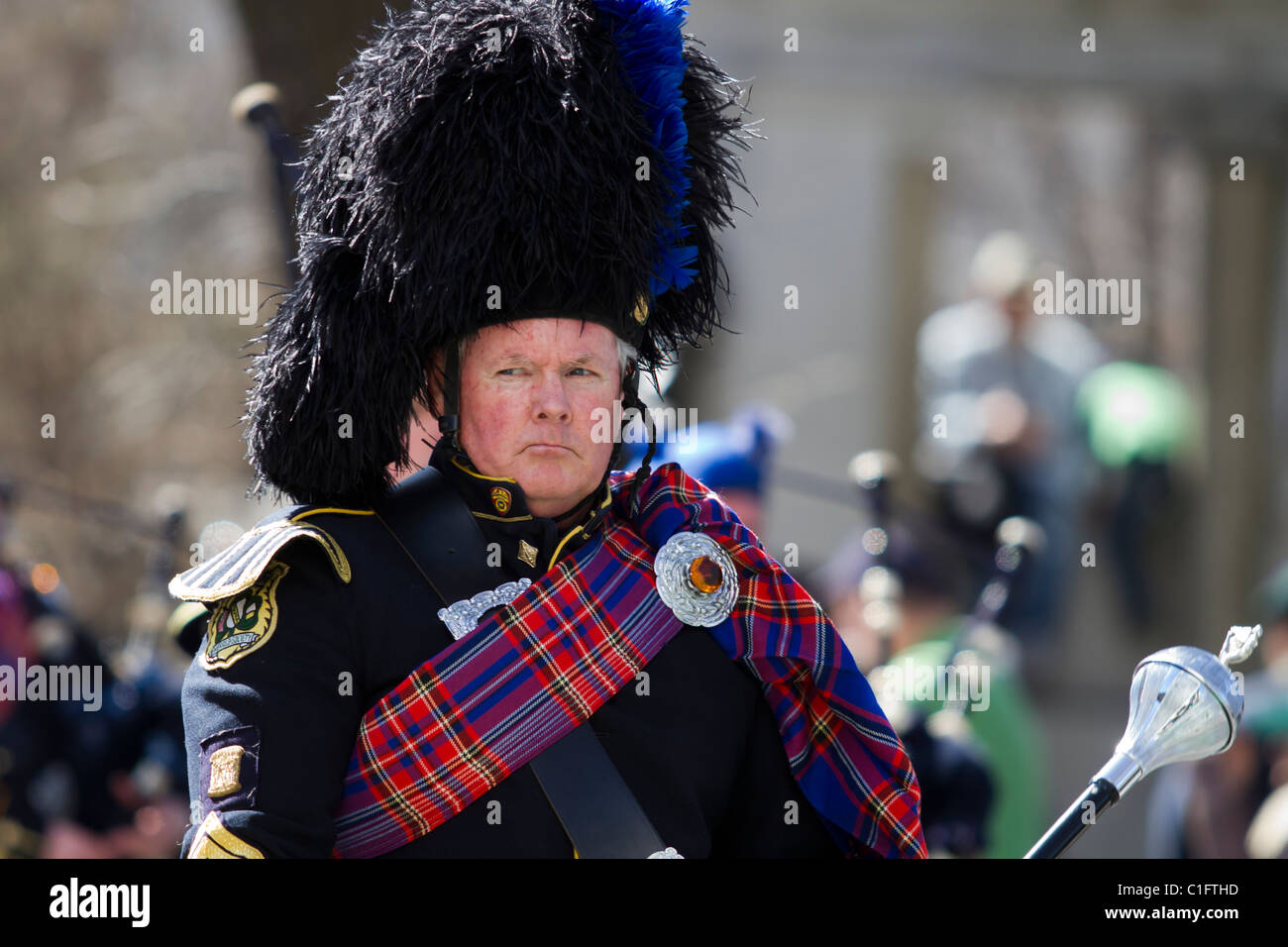 A grim looking Drum Major leads the Suffolk County Police Department's Emerald Society Pipe and Drum Band - Stock Image