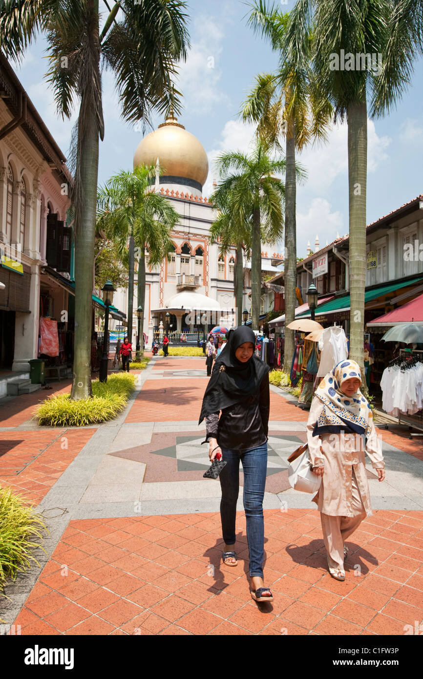 Malay women walking along Bussorah Street with Sultan Mosque in background.  Arab Quarter, Singapore - Stock Image