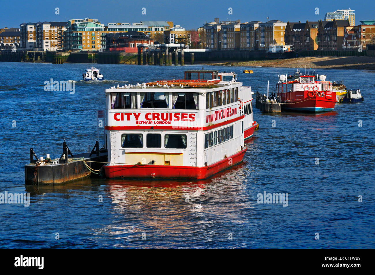 City cruise riverboat M.V. Eltham moored on River Thames with modern apartments along the banks, London, UK - Stock Image
