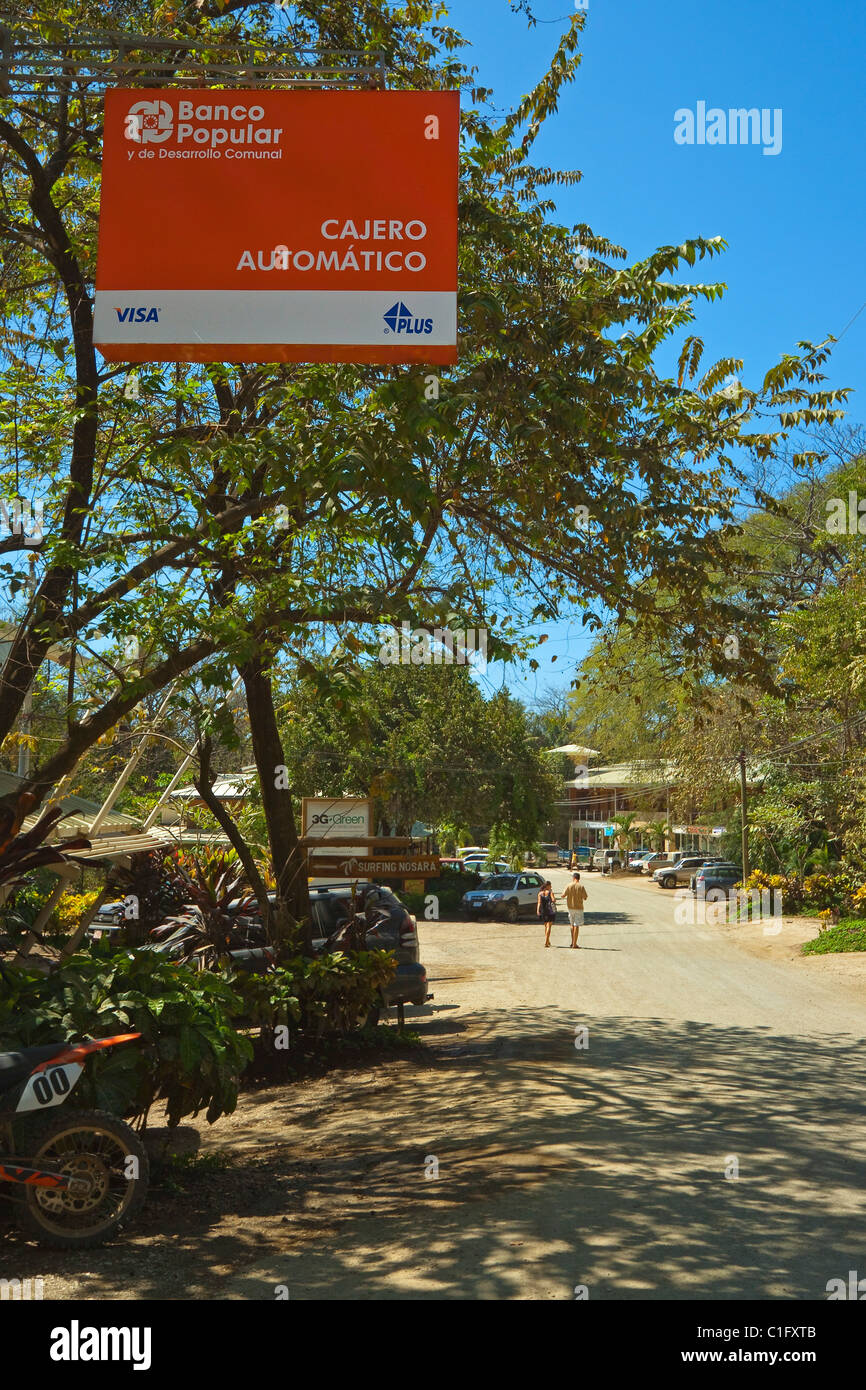 Sign for Banco Popular bank  over the main shopping street at this expatriate green zone surf community, Nosara, - Stock Image