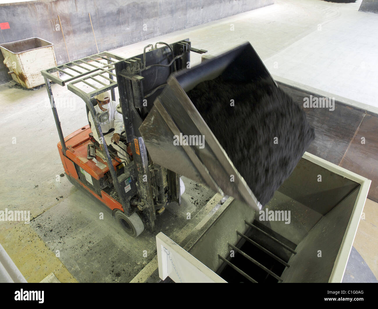 Man using special forklift truck with scoop inside factory. Assendelft, the Netherlands - Stock Image