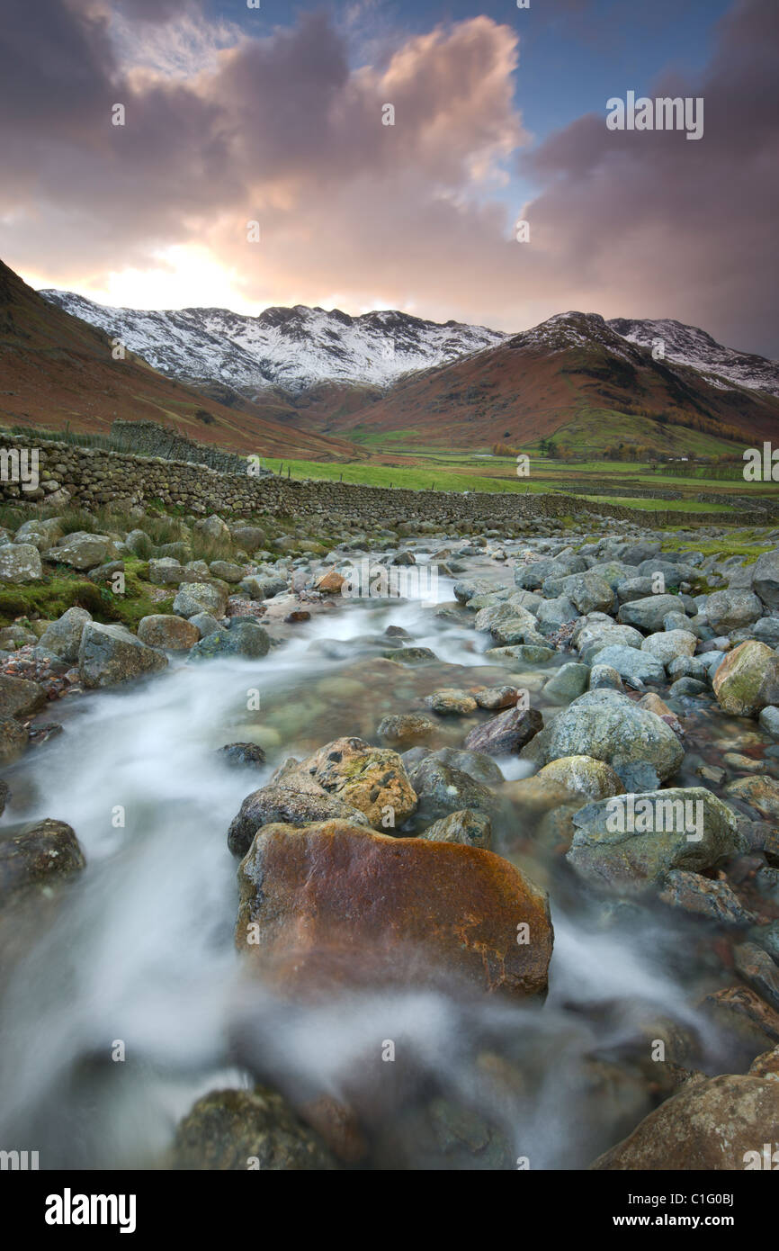 Redacre Gill river tumbling over rocks towards the snow capped mountains surrounding Great Langdale, Lake District - Stock Image