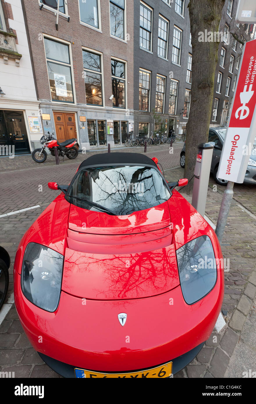 Electric Tesla sports car being charged at public recharging point in Amsterdam The Netherlands - Stock Image
