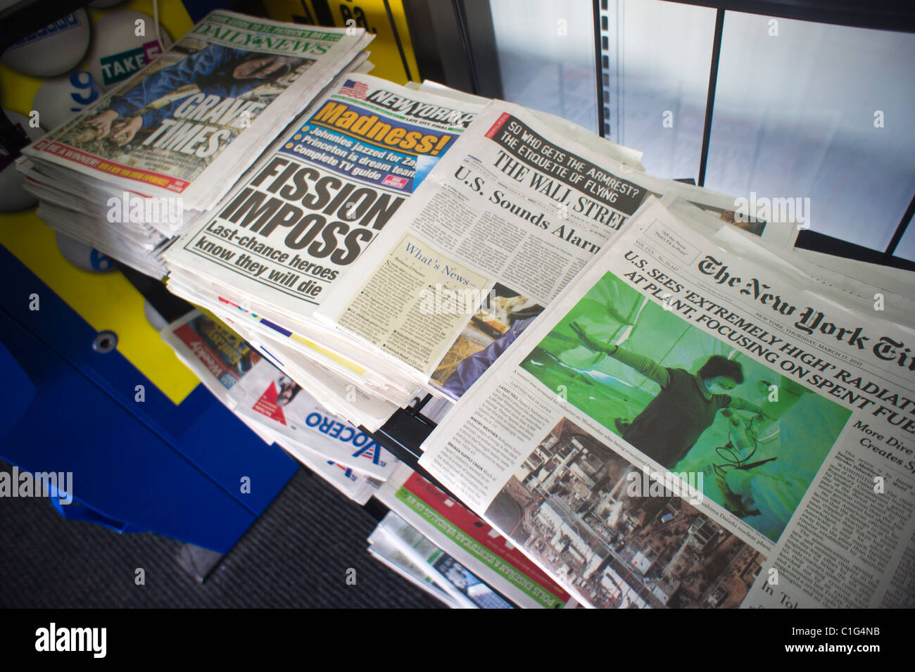Headlines of New York newspapers on a news stand report the ongoing nuclear crisis in Japan. - Stock Image