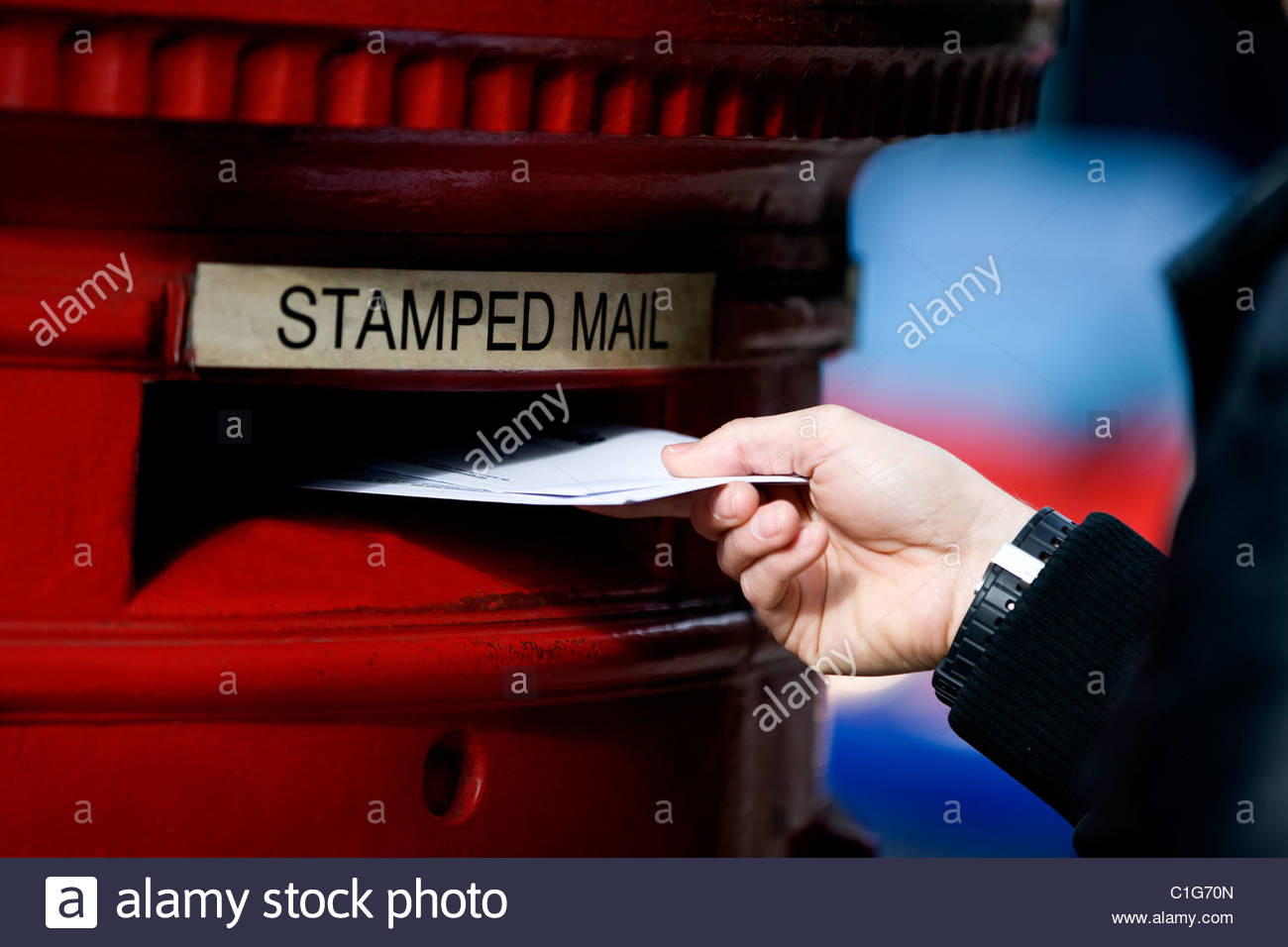 A man posting letters in a letterbox - Stock Image