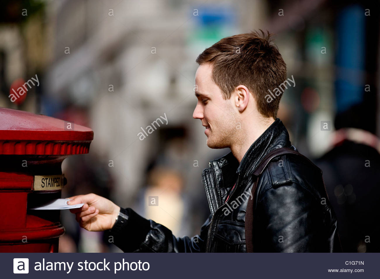 A man posting letters in a letterbox Stock Photo