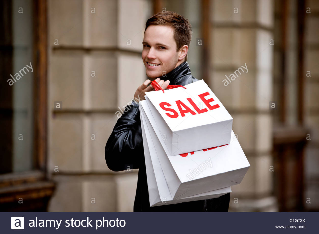A young man holding carrier bags - Stock Image