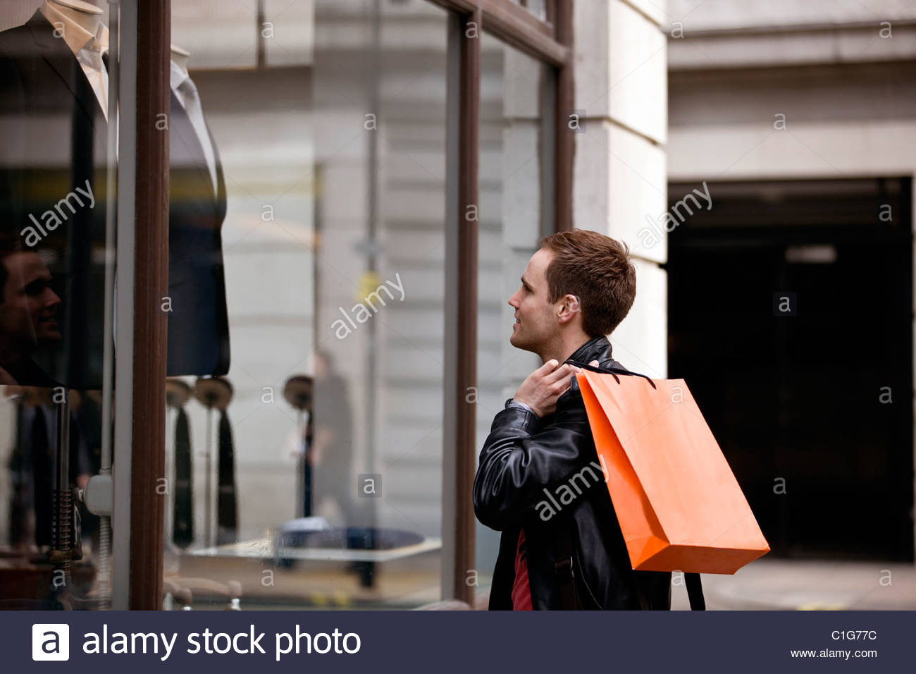 A young man looking in a shop window - Stock Image