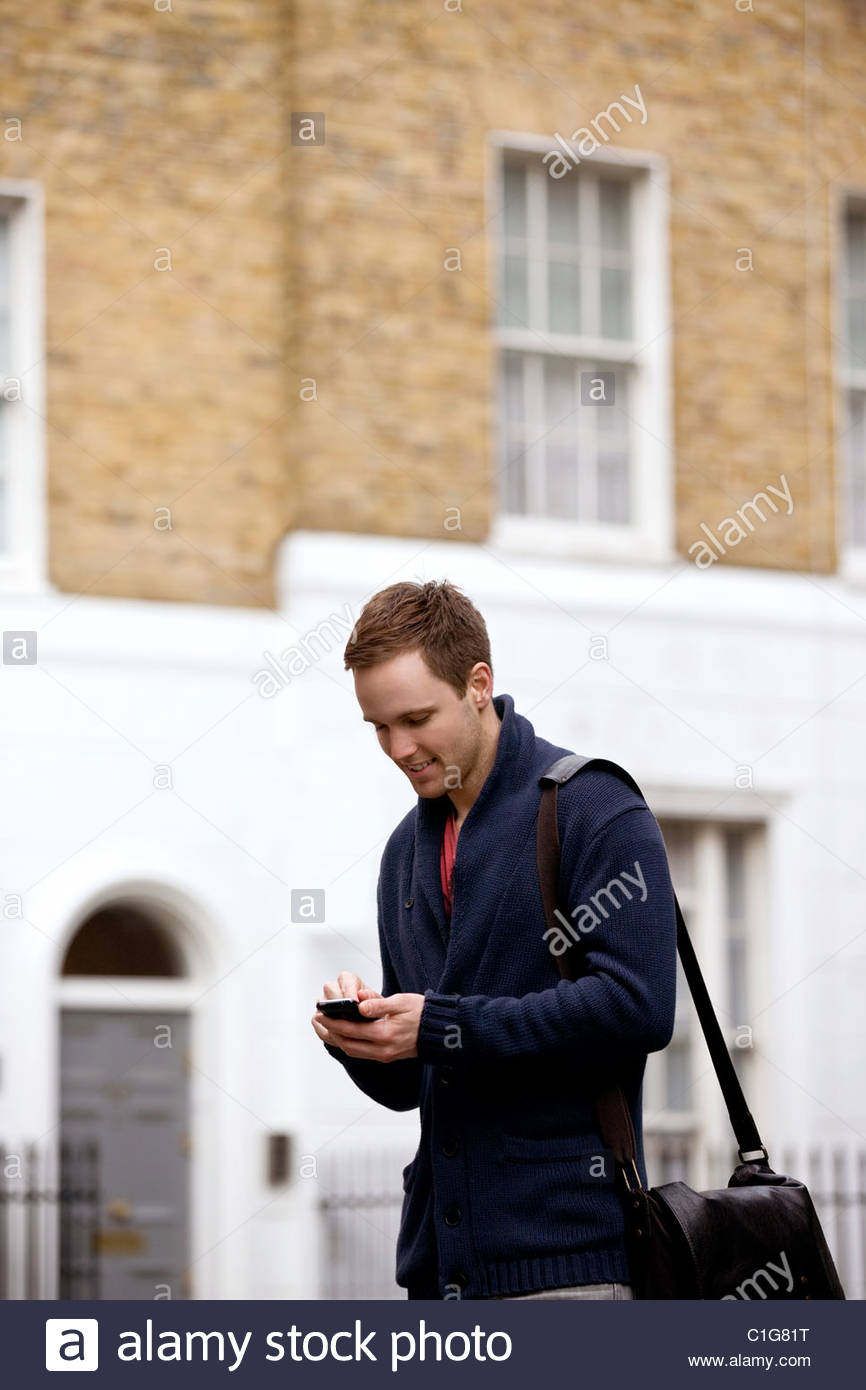 A young man standing in the street, using his mobile phone - Stock Image