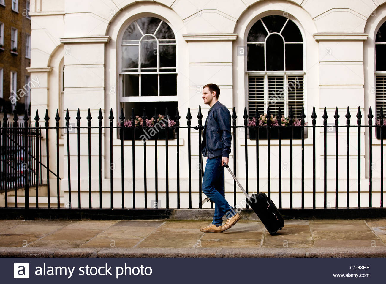 A young man pulling his suitcase in the street - Stock Image