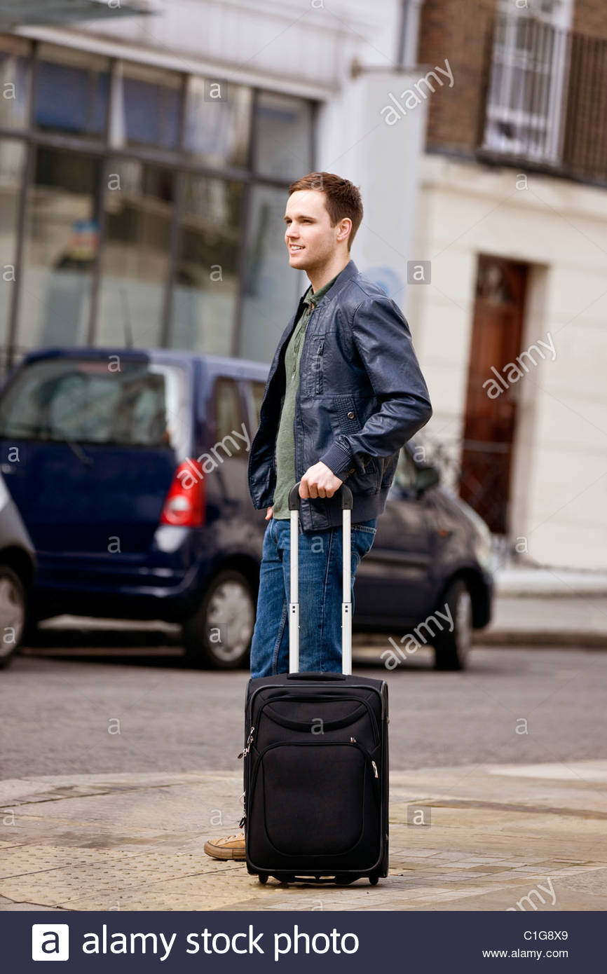 A young man standing in the street, holding his suitcase Stock Photo