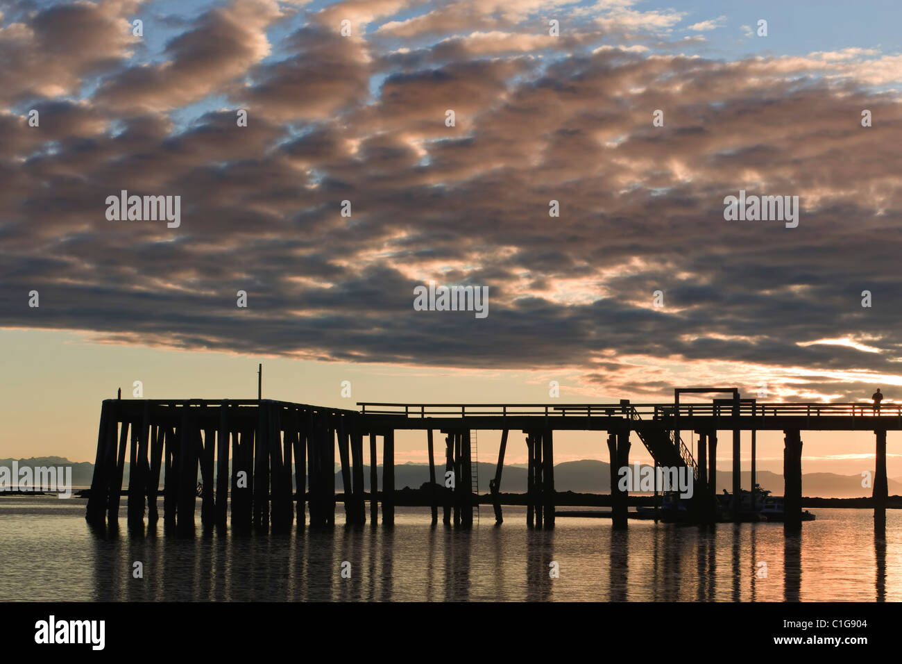 The dock at Kake, Kupreanof Island, in the Inside Passage of Southeast Alaska, in silhouette at sunset in the summer. - Stock Image
