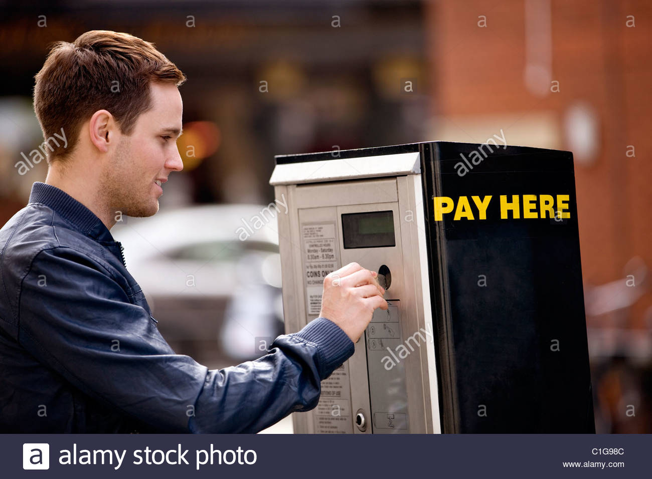 A young man putting coins in a parking meter Stock Photo