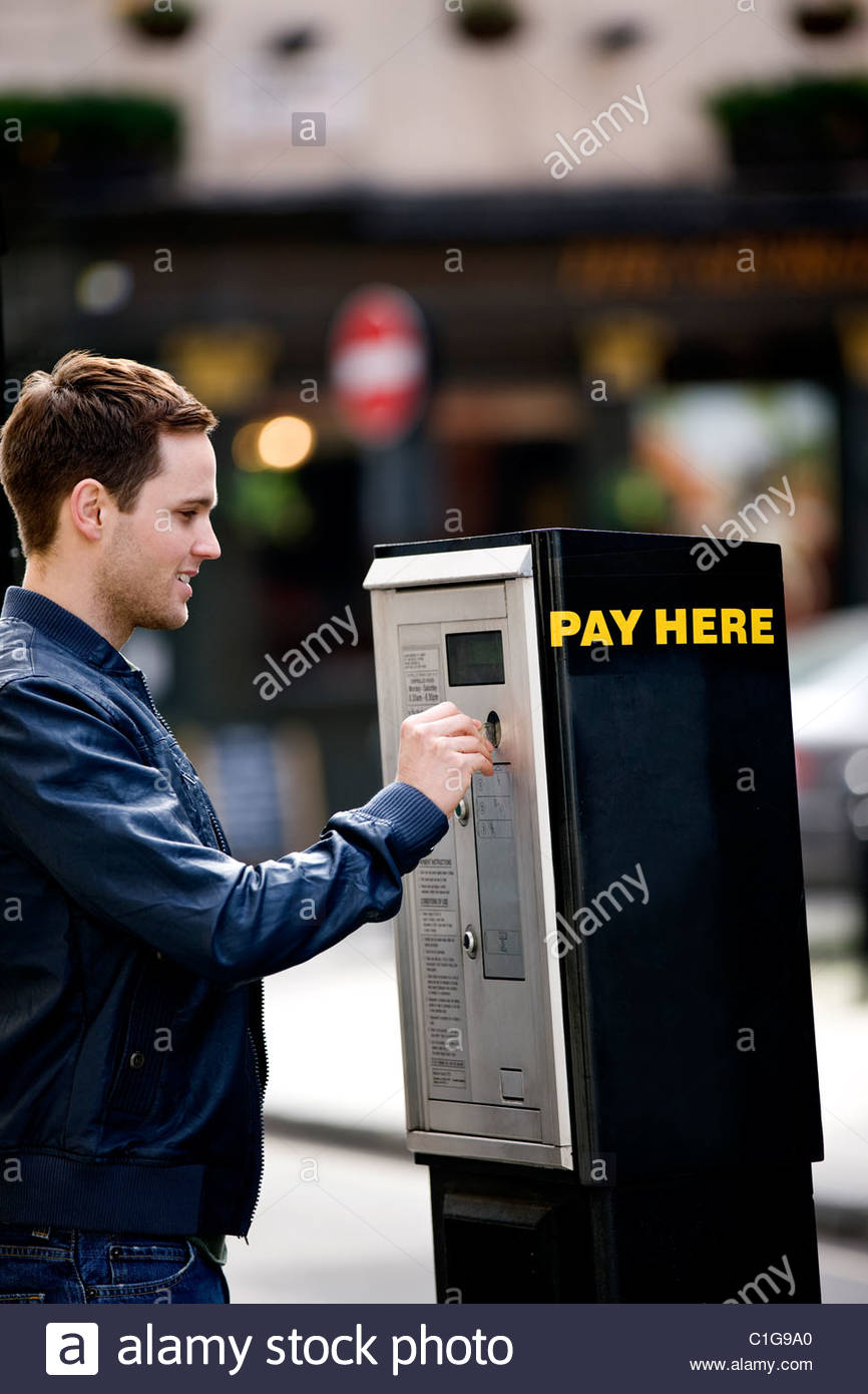 A young man putting coins in a parking meter - Stock Image