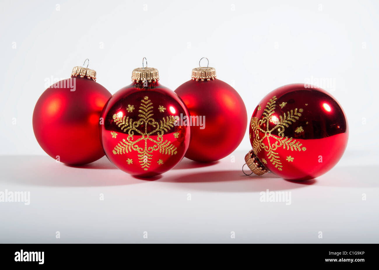 4 red Christmas tree baubles - Christmas decorations pair of satin and 2 shiny with gold snowflake paterns - Stock Image