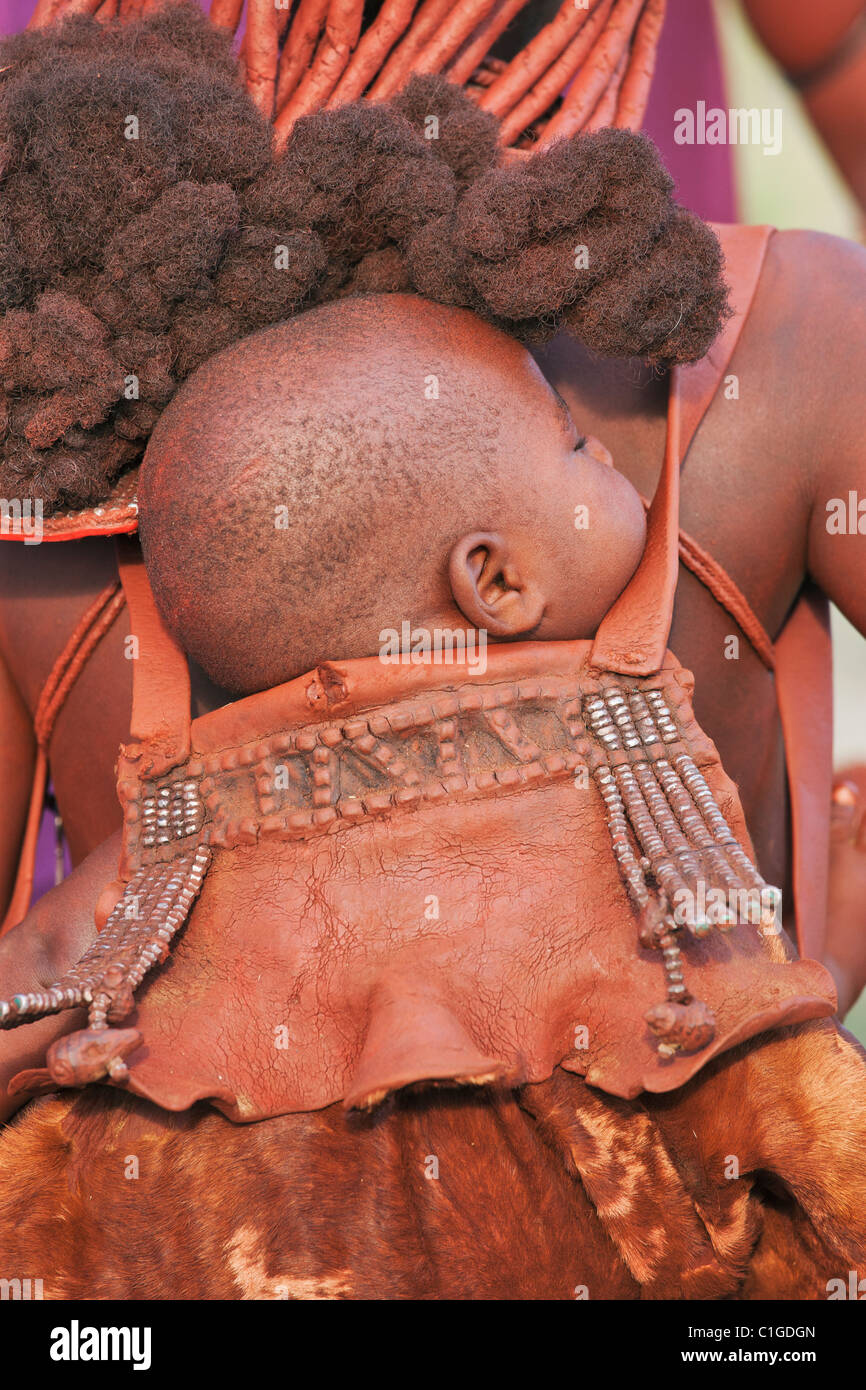 Himba baby in traditional pouch who live in the Kunene Region, Namibia - Stock Image