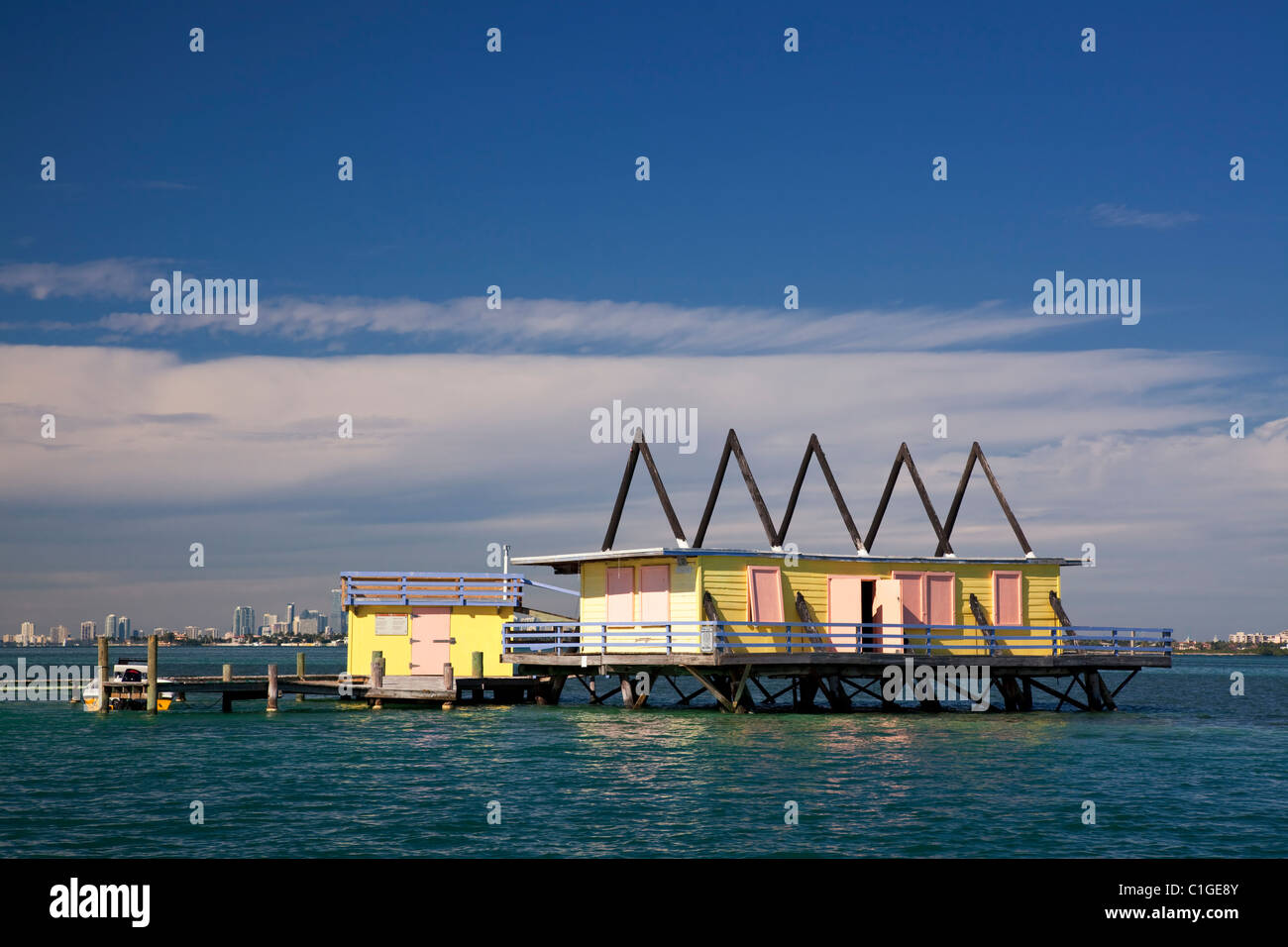 Colorful old Stilt house in Biscayne Bay, Miami skyline in background low clouds below deep blue sky, copy space - Stock Image