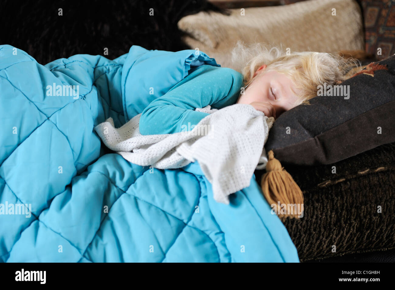 Stock photo of a poorly 5 year old girl resting on the setee. - Stock Image