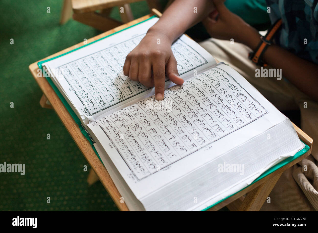 Young boy reading the Qur'an.   Little India, Singapore - Stock Image