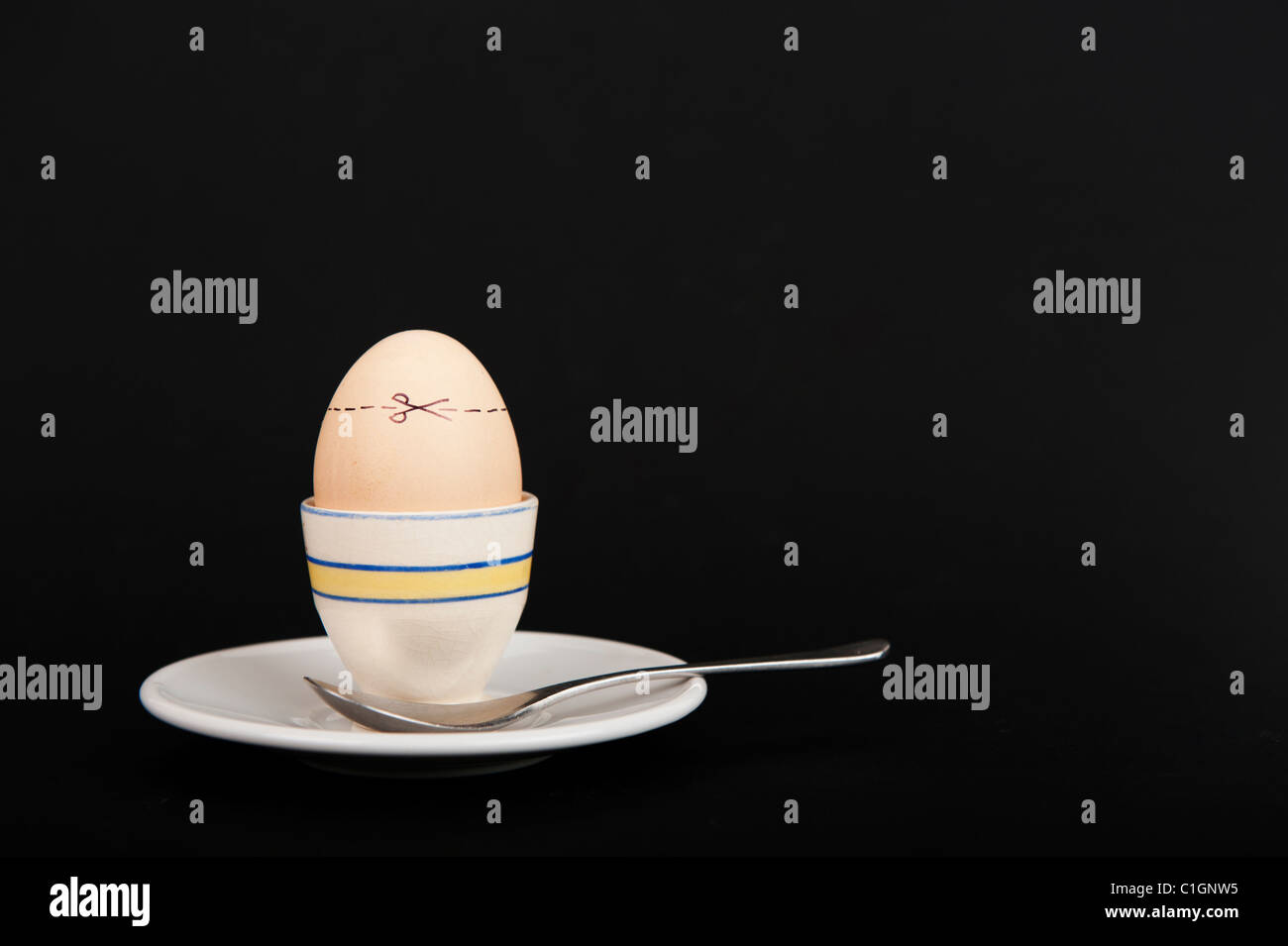 Stock photo of an egg in an egg cup with cut here lines across the shell. - Stock Image