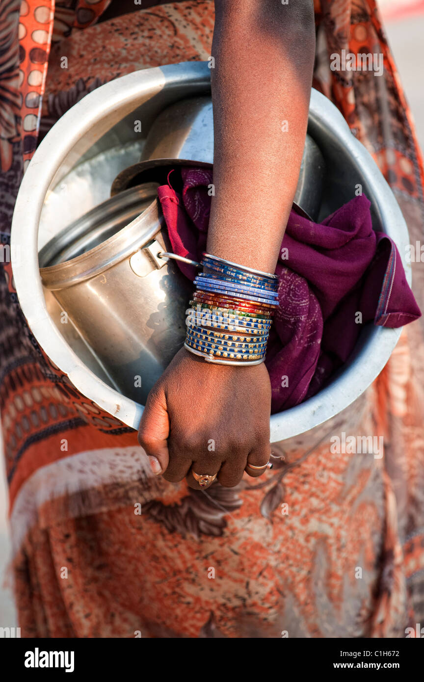 Indian woman holding a metal cooking pot with bangles on her arm. materila - Stock Image