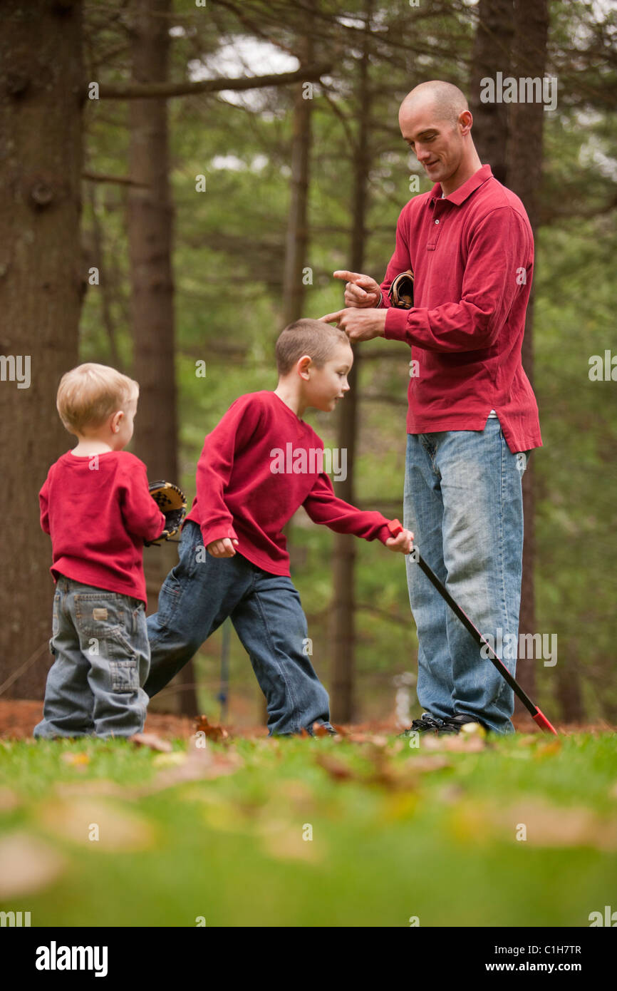 Man signing the word 'Careful' in American Sign Language while communicating with his sons in a park - Stock Image