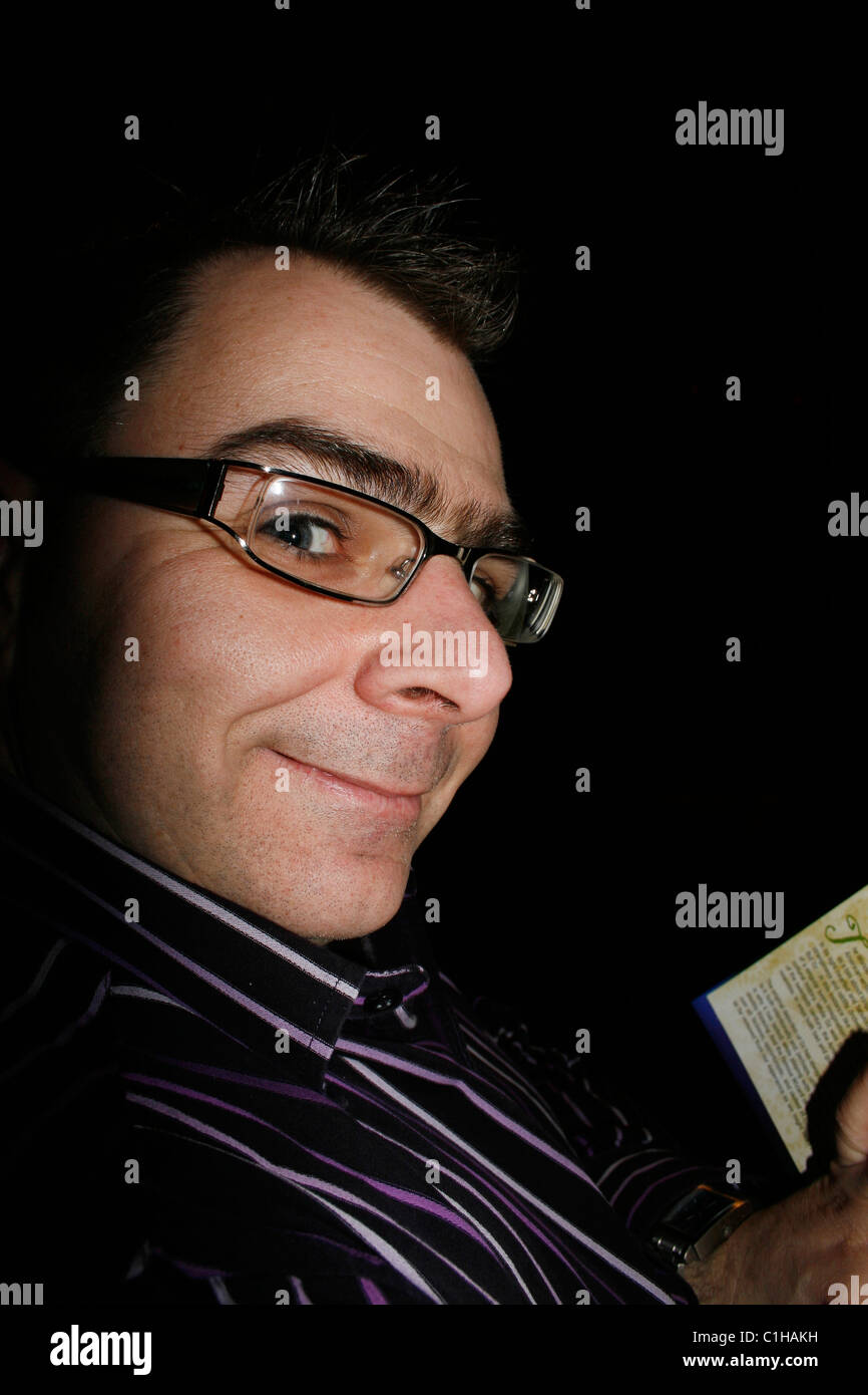 man reading program for play at a theatre Stock Photo